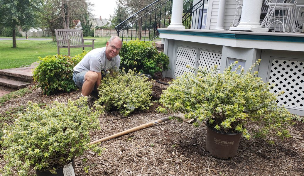 man planting bushes near porch
