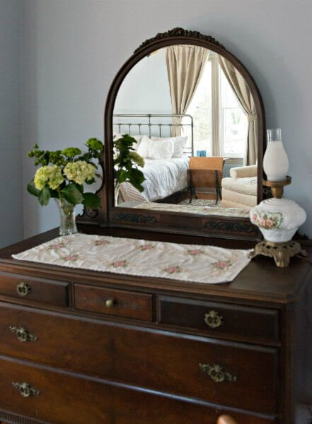 Brown vintage wooden vanity, a vase of several light green flowers, a gas lamp and mirror reflecting the bedroom