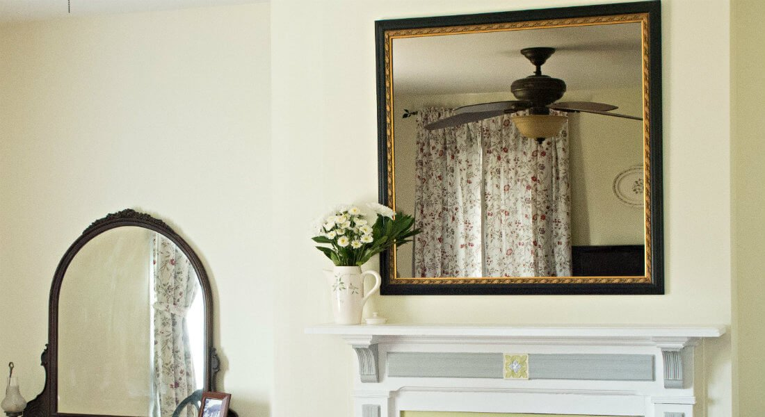 Bright cream room with white fireplace mantel and vintage vanity mirror