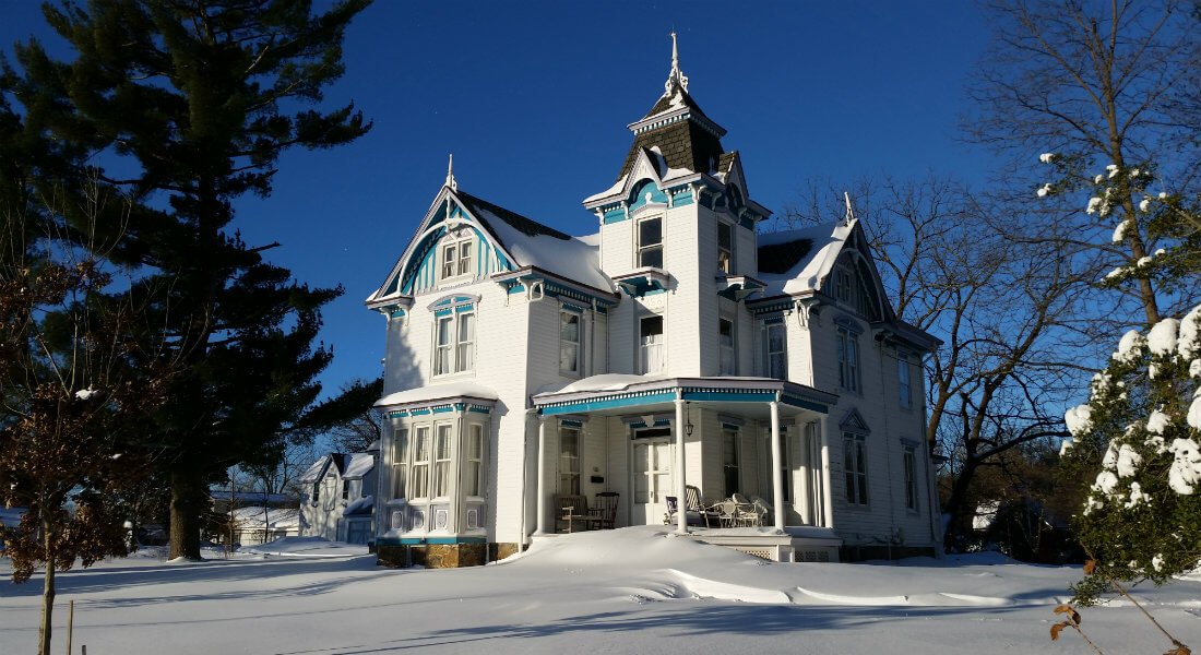 Large white Victorian house with grey and blue detailing covered in snow