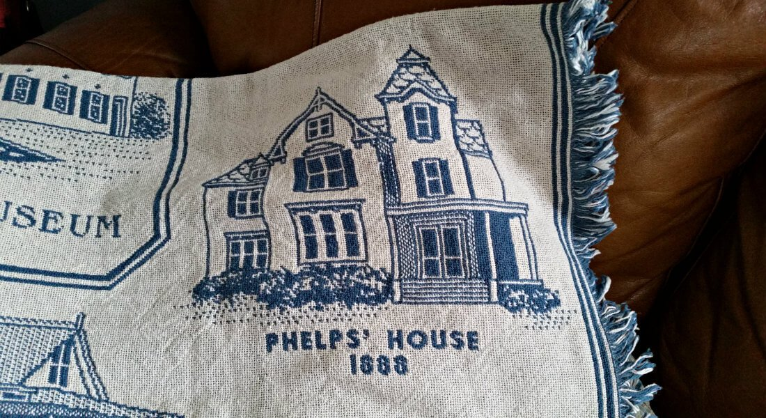 Blue and white blanket with short fringes that says Phelps House 1888