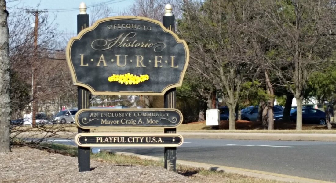 Large exterior black and beige sign that says welcome to historic laurel, an inclusive community, playful city USA