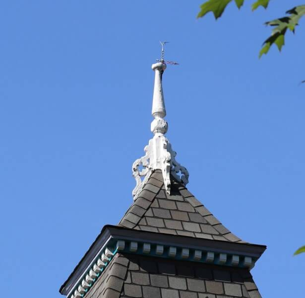 Original Spire:  White spire on peak of roof with the blue-sky background.