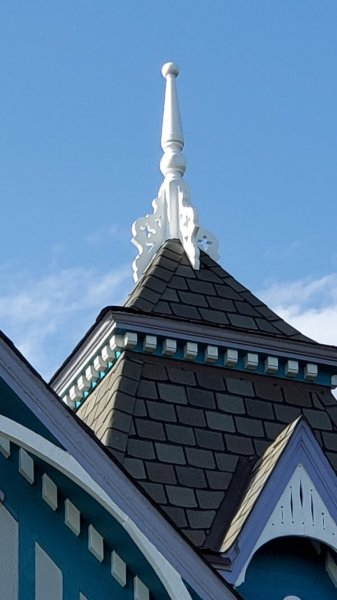 Finished spire--painted white and attached to peak, with dental trim visible below the first roof line and two other roof lines visible.