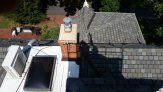 View looking down on the roof, showing shadow of Dave in the lift, the 3rd-floor skylight, the chimney, and the patio far below.