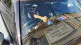 Picking up spire:  Reverse image of car windshield, with new spire visible inside car and Mark Supik sign visible as a reflection.