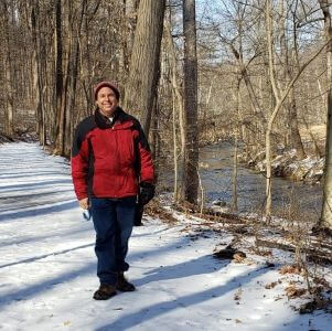 Man in red winter jacket stands on snowy trail next to river