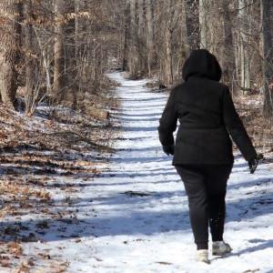 Woman in black coat walks in woods on snowy trail