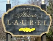 Exterior black and beige sign that says welcome to historic laurel, detailed with a line of yellow flowers
