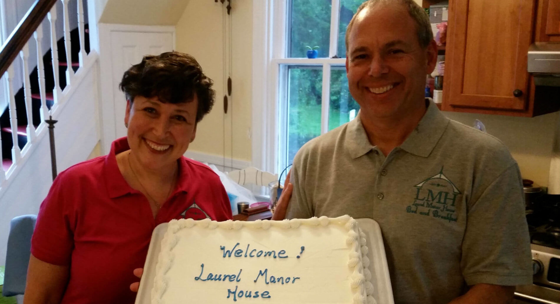 "Women in red shirt and man in grey shirt, both smiling, hold cake that says ""Welcome to Laurel Manor House""."