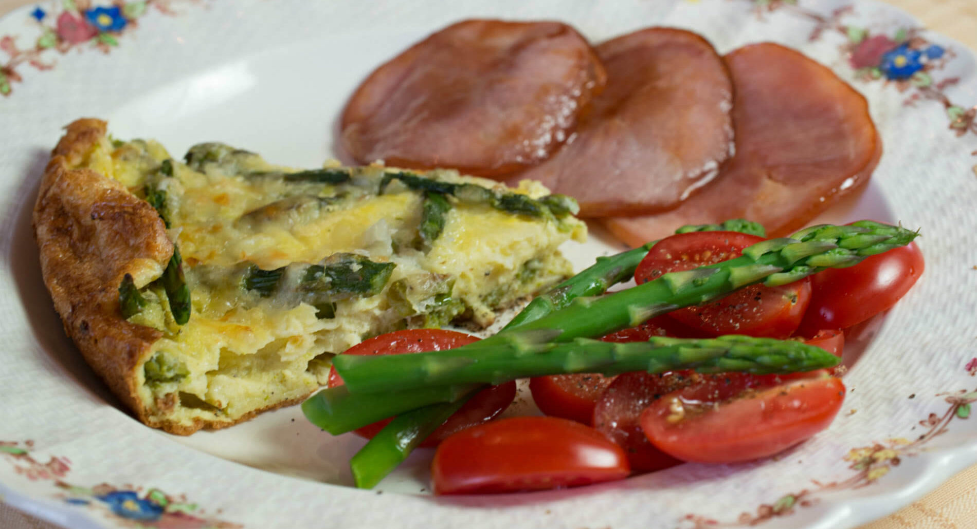 A white plate displaying a quiche, Canadian bacon, bright green asparagus and vibrant red cherry tomato slices