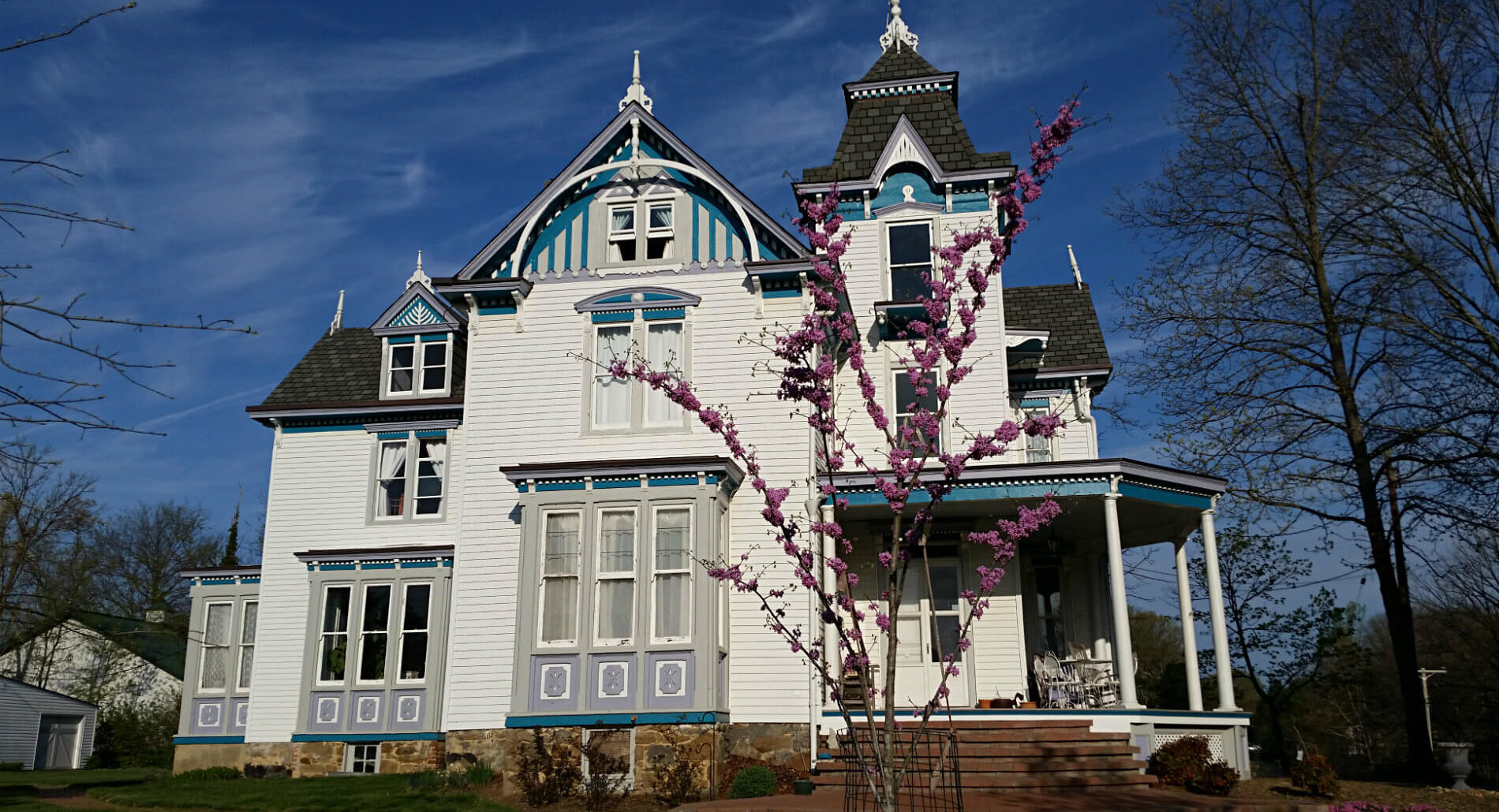 Large white Victorian styled house with blue and grey detailing and black shingles