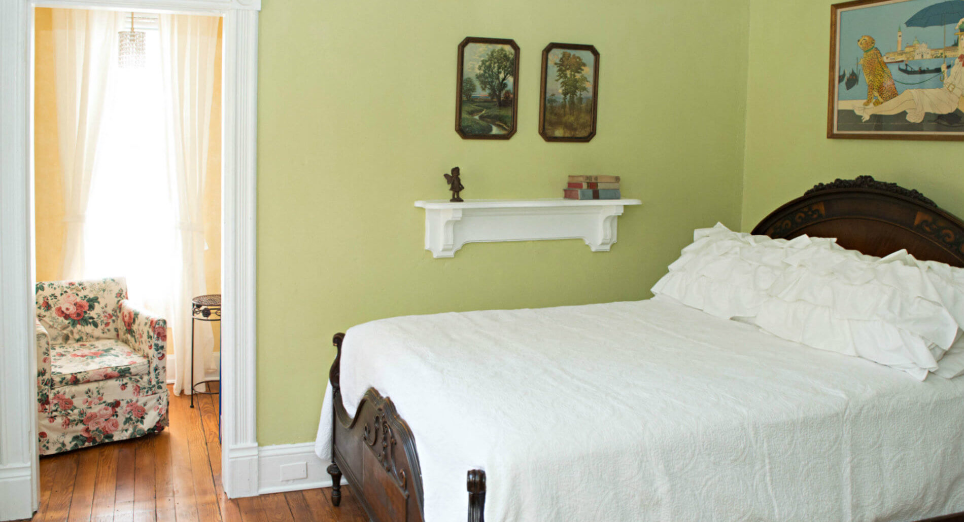 Light green room with white bedding, hardwood flooring, doorway to a yellow sitting room with a floral cushioned chair