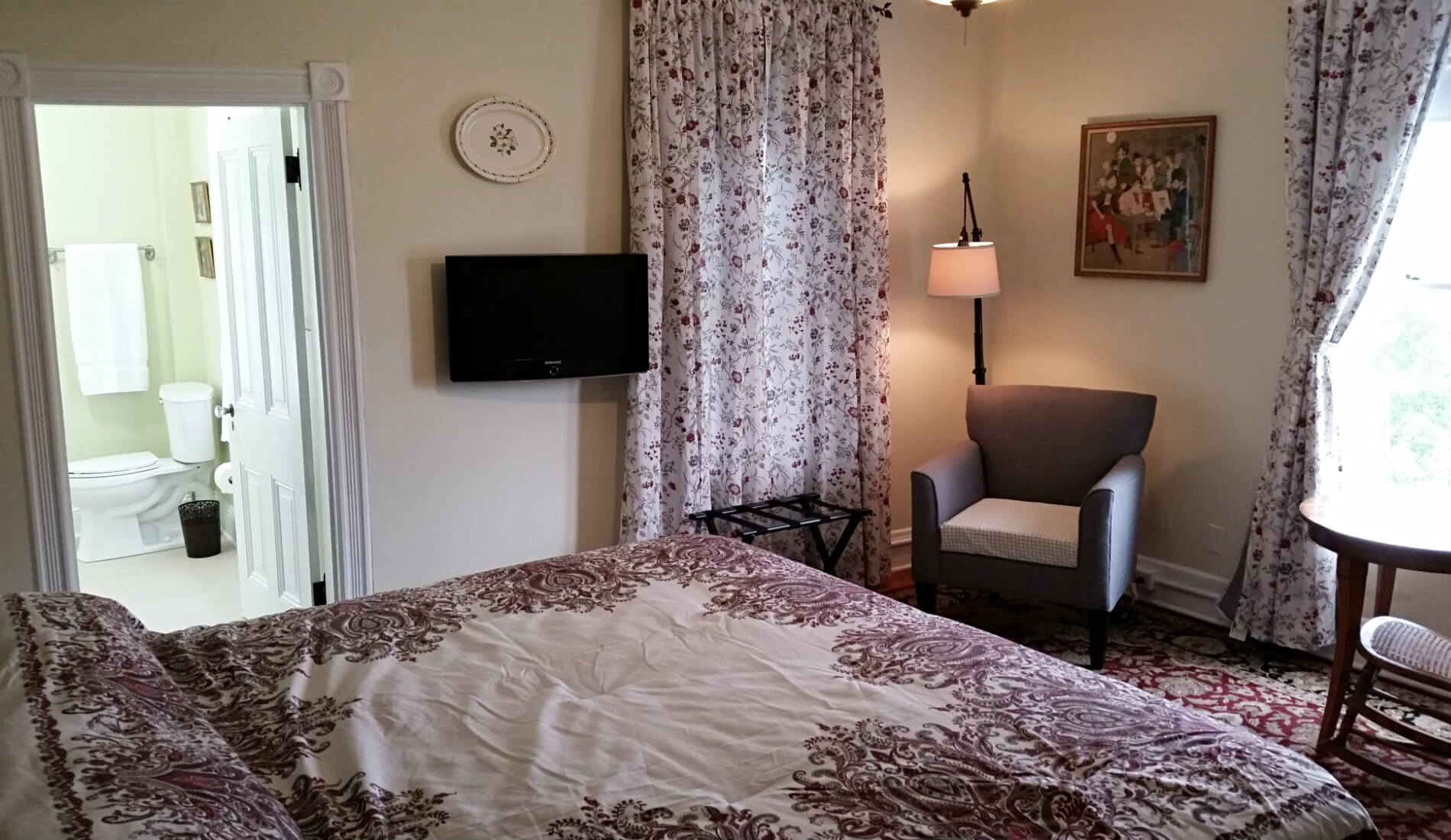 Beige guest room with burgundy and ivory bedding, flat screen tv, a chair and reading lamp