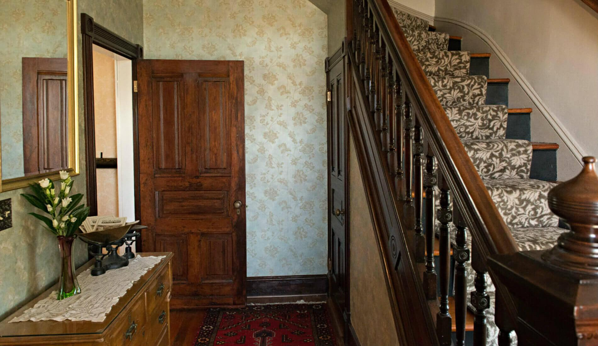 Cream wallpapered hallway with brown wooden staircase to the right and a wooden decorative table against the left wall