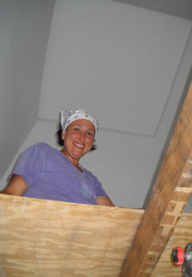 Woman in a purple shirt with white handkerchief headband working inside