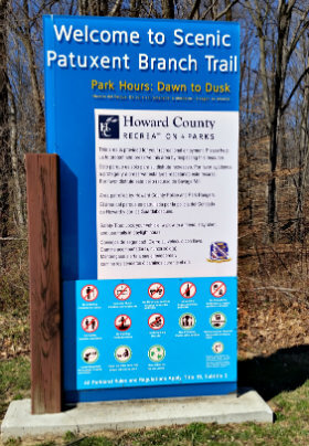 Large exterior blue sign attached to a wooden brown post which says welcome to scenic patuxent branch trail