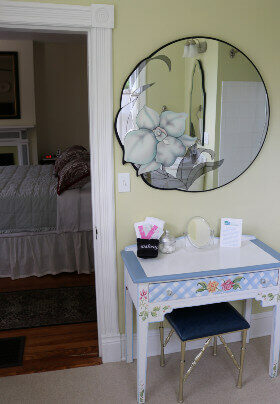 Vanity table with blue seat. Circular mirror with floral design on wall. Through doorway is bedroom; bed has white coverings, red pillows.