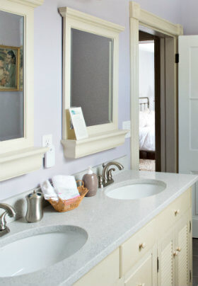 Light purple bathroom with duel rounded sinks, a cream vanity and two cream framed mirrors
