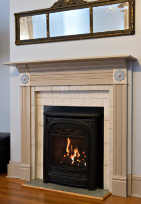 Small black fireplace framed with a beige mantel beneath a mirror