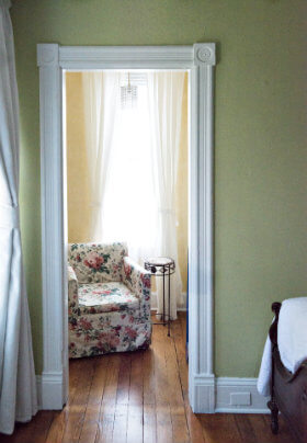 White framed doorway into a yellow room with a floral chair and small metal side table